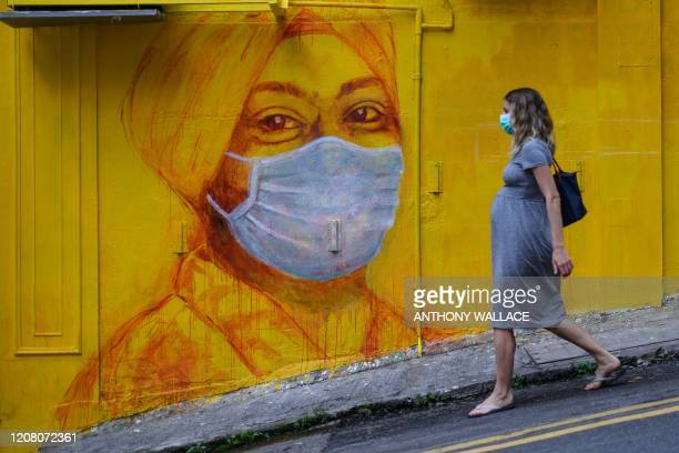 Pregnant woman wearing a face mask as a precautionary measure walks past a street mural in Hong Kong, on March 23 after the citys Chief Executive...