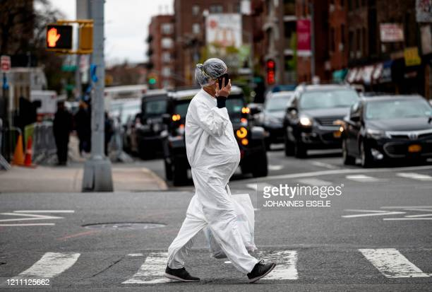 Pregnant woman wearing a hazmat suit and a mask walks in the streets in the Elmhurst neighbourhood of Queens on April 27, 2020 in New York City. - In...