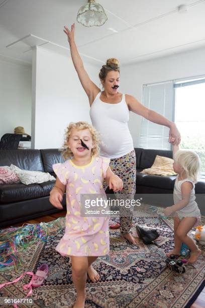 a pregnant woman wearing a moustache dances in a messy room with her children - grossesse humour photos et images de collection