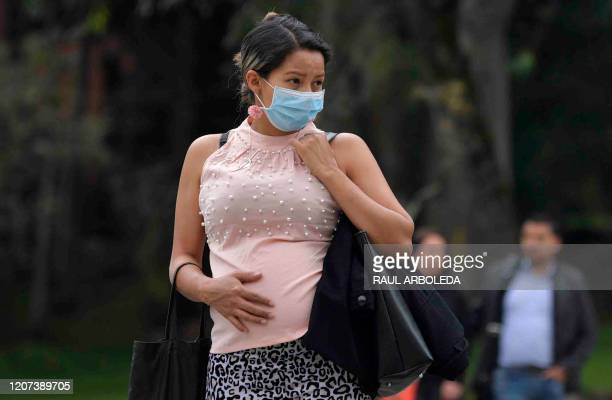 Pregnant woman wears a face mask as a preventive measure against the spread of the new coronavirus, COVID-19, as she waits for the bus in Bogota, on...