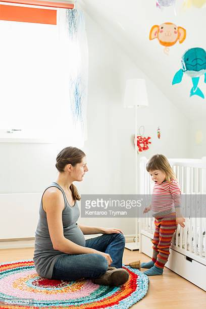 Pregnant woman with daughter at home