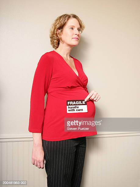 pregnant woman with fragile sticker on stomach, side view - fragile sticker stock pictures, royalty-free photos & images
