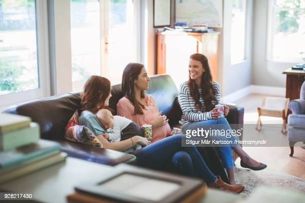 pregnant woman with friends and baby boy on sofa - gossip stock pictures, royalty-free photos & images