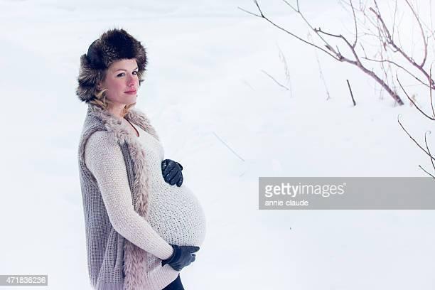 donna incinta con cappello di pelliccia posign in un paesaggio di neve - gennaio foto e immagini stock