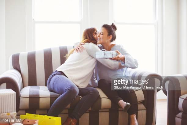 zwangere vrouw met gave omhelst vriend op bank - ontvangen stockfoto's en -beelden