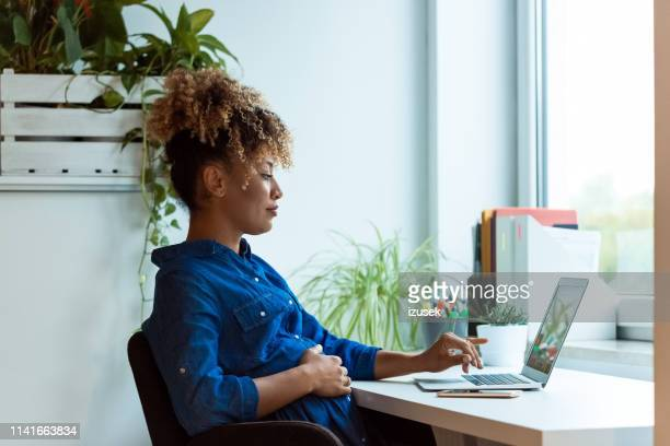 pregnant woman with hand on belly using laptop - pregnant stock pictures, royalty-free photos & images
