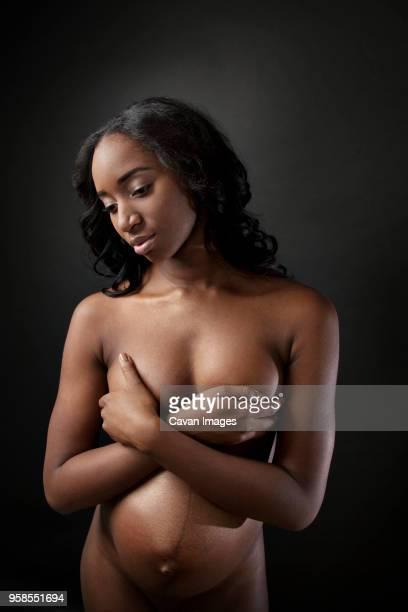 pregnant woman with hands on breast looking down while standing against black background - weibliche brust schwanger stock-fotos und bilder