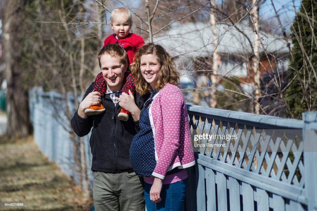 Pregnant woman with her husband and little girl : Stock Photo