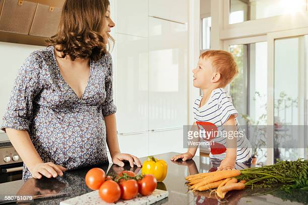 Pregnant woman with her little son in the kitchen