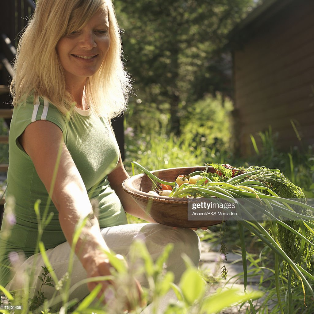 Pregnant woman with herbs and vegetables in baskets, smiling : Stock Photo