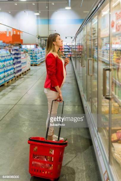 Schwangere Frau mit Einkaufsmöglichkeiten, stehend und auf der Suche