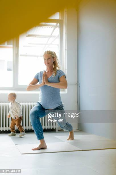 pregnant woman with toddler son practicing yoga - donne bionde scalze foto e immagini stock