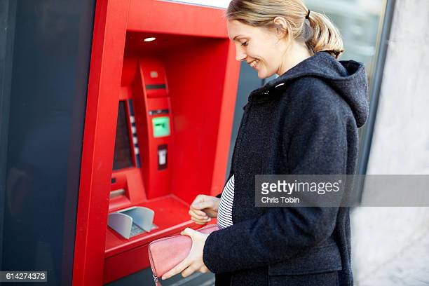 Pregnant woman withdrawing money from ATM