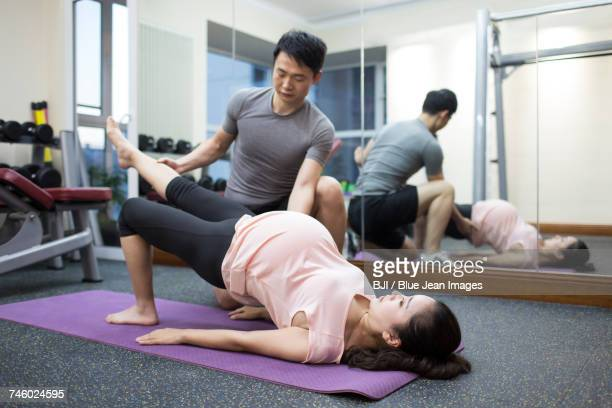 Pregnant woman working with trainer at gym