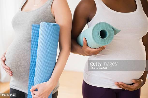 Pregnant women carrying yoga mats