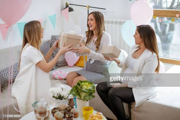 pregnant women exchanging gifts - baby shower stock pictures, royalty-free photos & images
