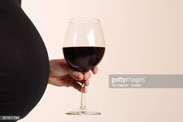 A pregnant women poses with a glass of red wine Photo Tim Clayton