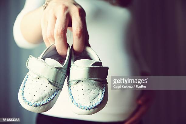 Pregnant Women Showing Baby Booties In Hand
