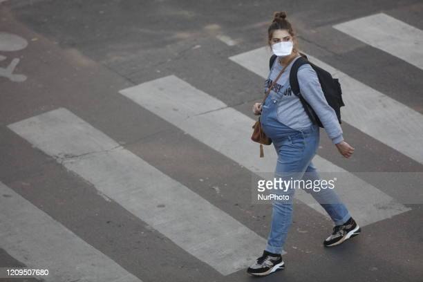 Pregnant women with a protective mask walks on the street in Paris, on April 8 during the lockdown in France to attempt to halt the spread of the...