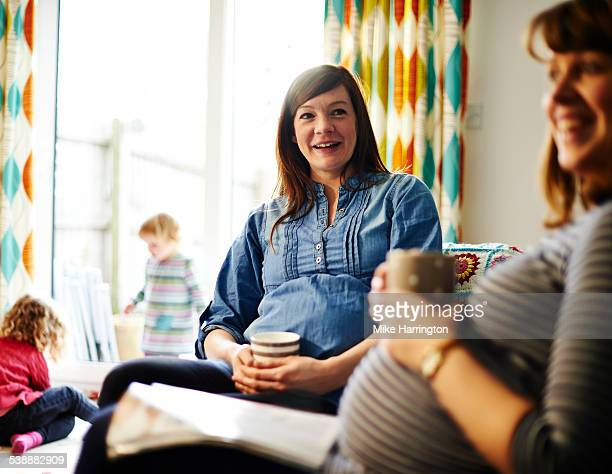 pregnant women with hot drinks in lounge. - pregnancy stock pictures, royalty-free photos & images