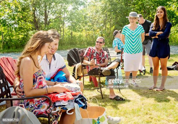 pregnant young couple opening gifts at baby shower outdoors. - baby shower stock pictures, royalty-free photos & images