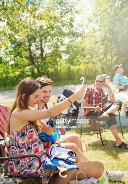 Gravida unga par öppnar presenter på babyshower utomhus.