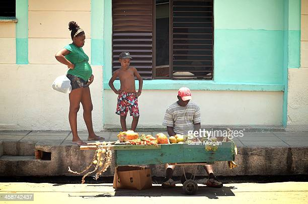 Pregnant young mother and her son stop in the street to buy vegetables in Cardenas, Cuba. Raul Castro's economic reforms have enabled small...