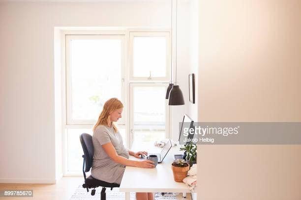 Pregnant young woman at desk typing on laptop
