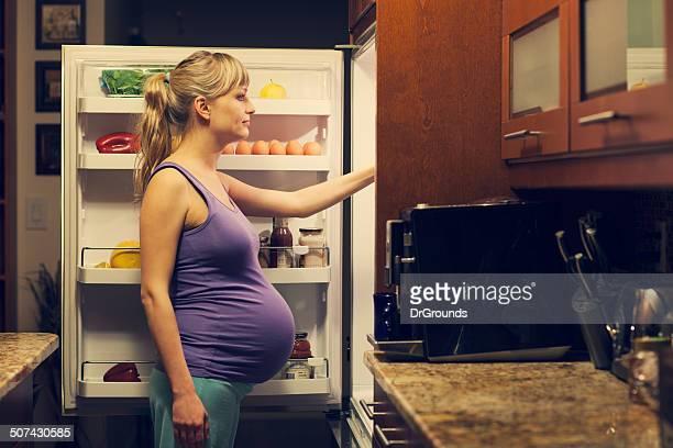 Schwangere Junge Frau im Kühlschrank Sie gesunde Speisen