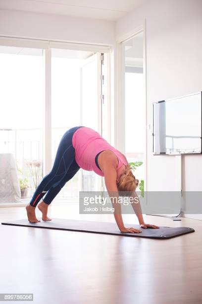 Pregnant young woman bending forward doing yoga exercise in living room