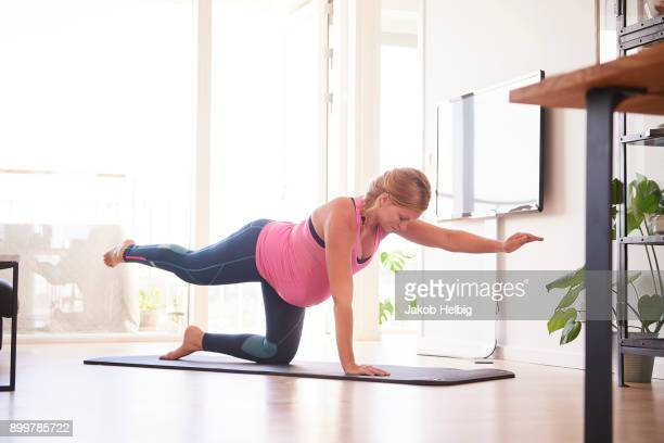 Pregnant young woman doing yoga exercise in living room