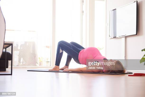 Pregnant young woman doing yoga exercise on mat