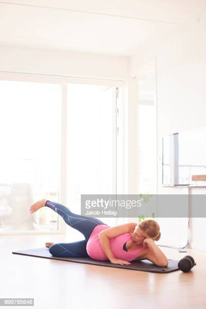 Pregnant young woman exercising on yoga mat in living room