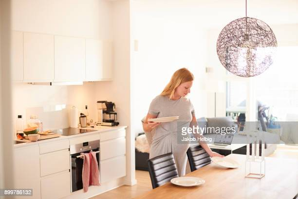 Pregnant young woman in laying the dining table