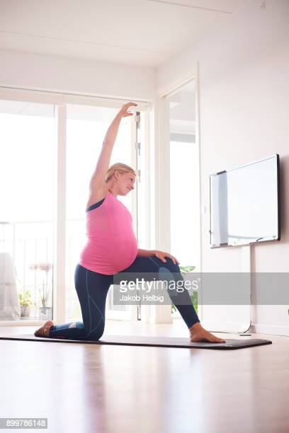Pregnant young woman kneeling doing yoga exercise in living room