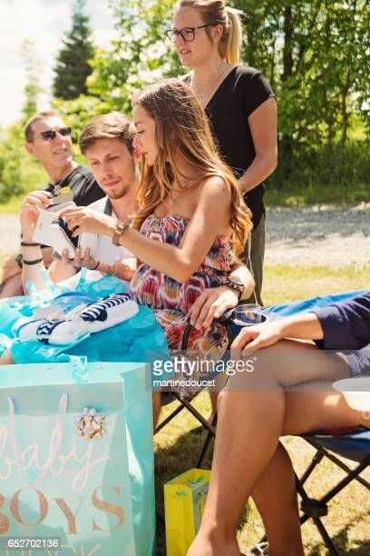 """pregnant young woman opening gifts at baby shower outdoors. - """"martine doucet"""" or martinedoucet stock pictures, royalty-free photos & images"""
