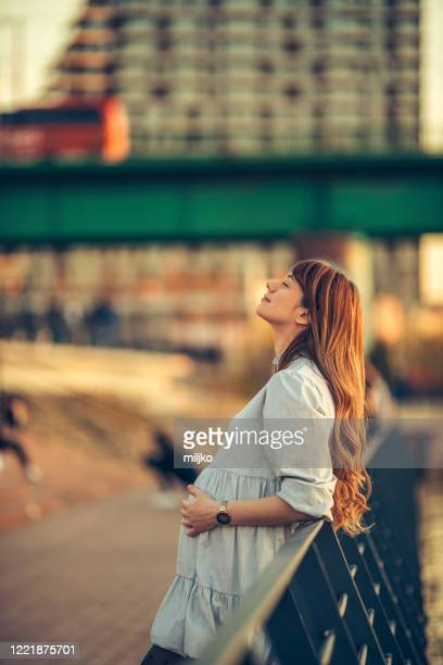 pregnant young woman relaxing on at sunset - miljko stock pictures, royalty-free photos & images