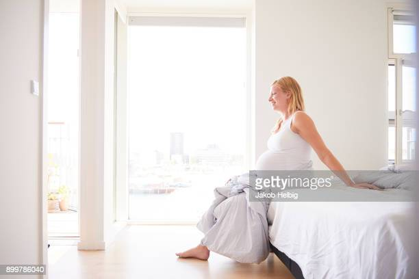 Pregnant young woman sitting on bed