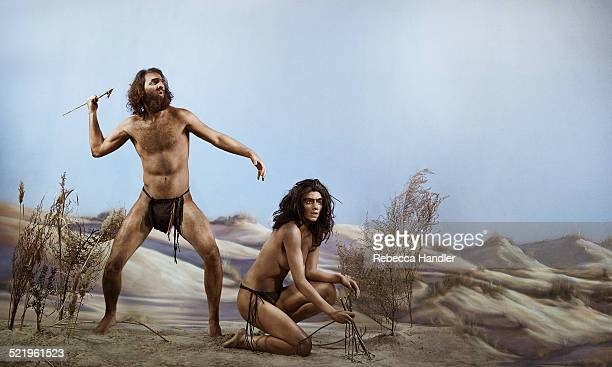 Prehistoric man next to  woman kneeling