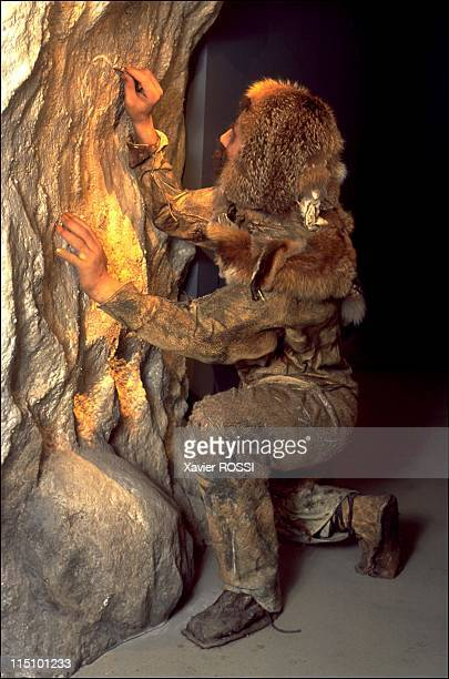 Prehistorical museum in Quinson, France on May 29, 2001 - Paleolithic period , a scene showing a Neanderthal man engraving a rock wall using a...