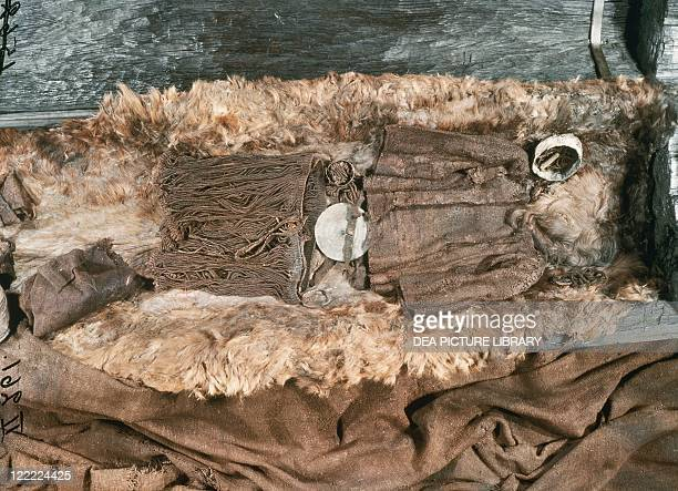 Prehistory Denmark Bronze Age Reconstruction of the tomb of the Egtved Girl with woolen bodice and string skirt and belt with a bronze disk From...
