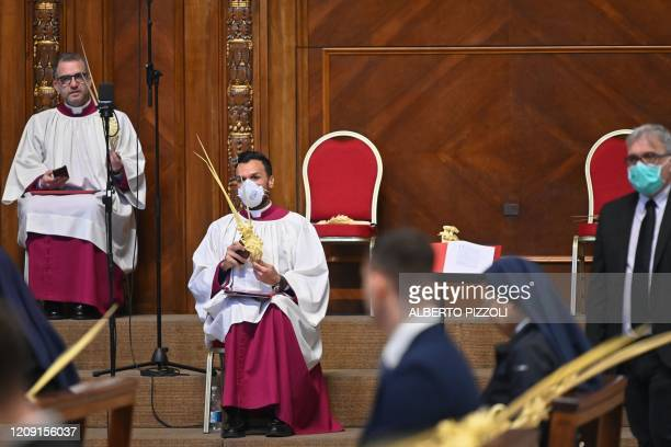 A prelate wearing a face mask holds a palm branch as attendees wait for the start of the Pope's Palm Sunday Mass behind closed doors in St Peter's...