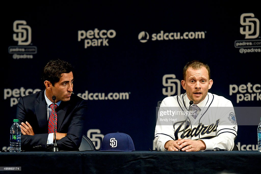 AJ Preller of the San Diego Padres listens to Andy Green at a press conference introducing him as the new Manager of the San Diego Padres at Petco Park on October 23, 2015 in San Diego, California.