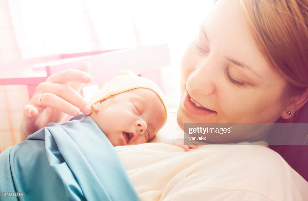 Premature baby girl resting on mother's breasts : Stock Photo