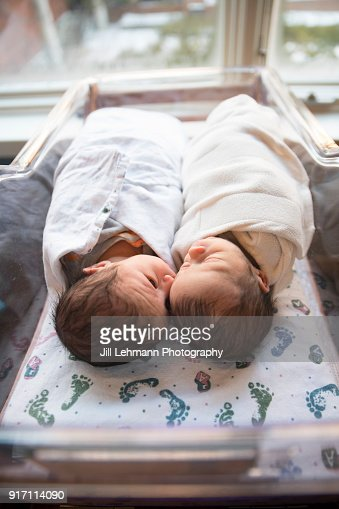 Premature Newborn Fraternal Twins in Hospital Sleep Together in Plastic Crib