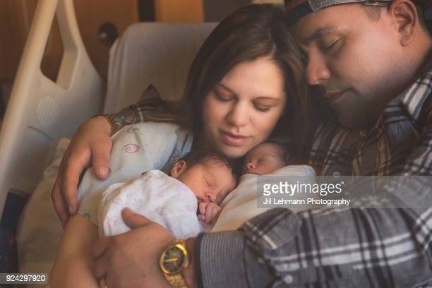 premature newborn fraternal twins snuggle up together with parents in hospital bed - home birth stock photos and pictures
