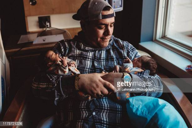 premature twins are held together by father in arms in hospital - twin stock pictures, royalty-free photos & images