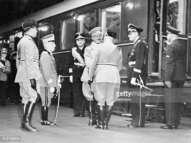 Premier Benito Mussolini of Italy back to camera is shown shaking hands with Adolf Hitler as the German Chancellor arrived here by train for his...