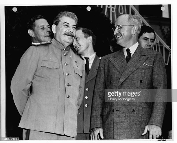 Premier Joseph Stalin and President Harry S Truman smiling during the Potsdam Conference Presidential advisor Charles E Bohlen stands in the...