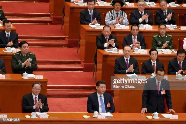 Premier Li Keqiang sits back next to Chinese President Xi Jinping after his speech during the opening session of the National People's Congress at...